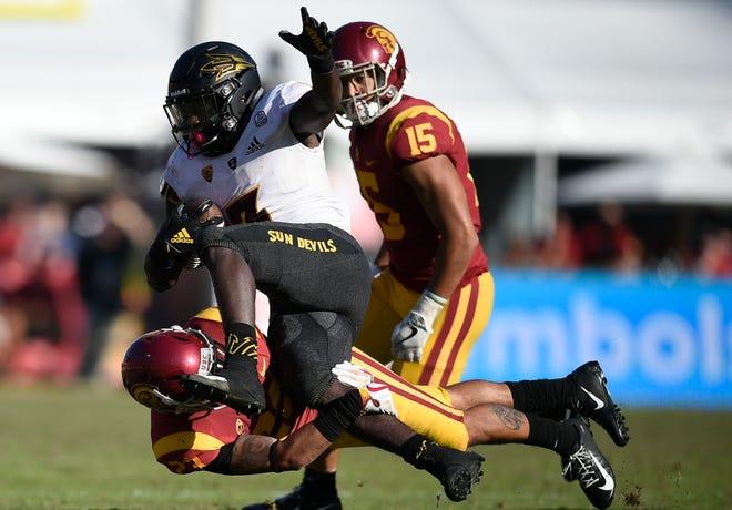 ASU running back Eno Benjamin runs the ball while USC cornerback Jonathan Lockett tries to bring him down during the second half of a game at the Los Angeles Memorial Coliseum.