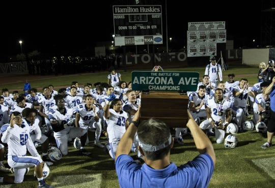 """Chandler head coach Shaun Aguano holds up the """"The Battle"""" trophy after their 49-7 win over crosstown rival Hamilton, Friday, Oct. 26, 2018. #azhsfb"""