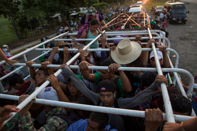 Migrants travel on a cattle truck, as a thousands-strong caravan of Central American migrants slowly makes its way toward the U.S. border, between Pijijiapan and Arriaga, Mexico, Friday, Oct. 26, 2018. Many migrants said they felt safer traveling and sleeping with several thousand strangers in unknown towns than hiring a smuggler or trying to make the trip alone.