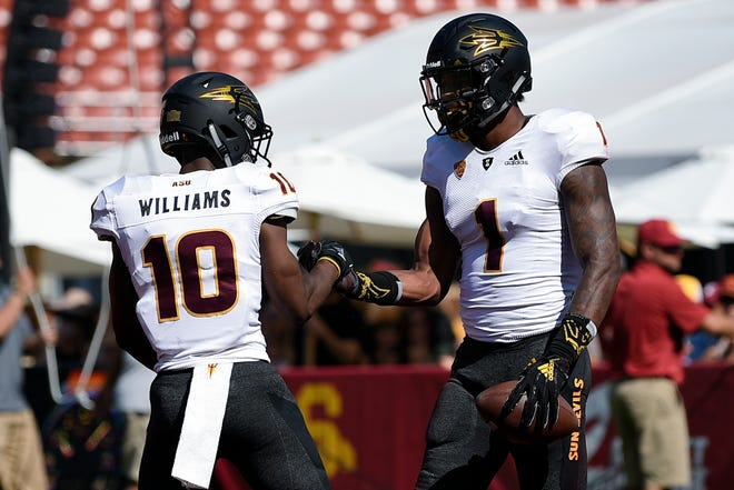 N'Keal Harry (1) celebrates with Kyle Williams (10) after scoring a touchdown against USC in the first half of a game at the Los Angeles Memorial Coliseum.