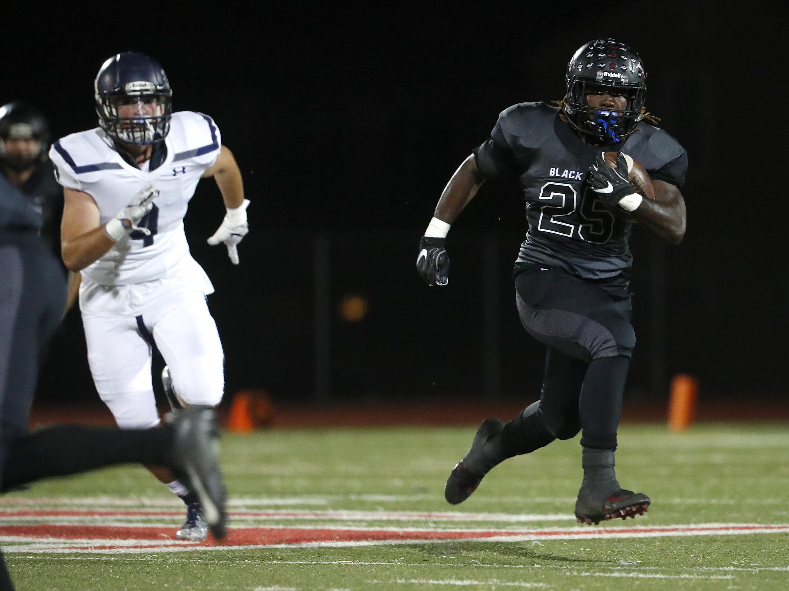 Williams Field's Jaden Thompson (25) runs past Higley's Connor Mills (4) during the first half at Williams Field High School in Gilbert, Ariz. on October 26, 2018.