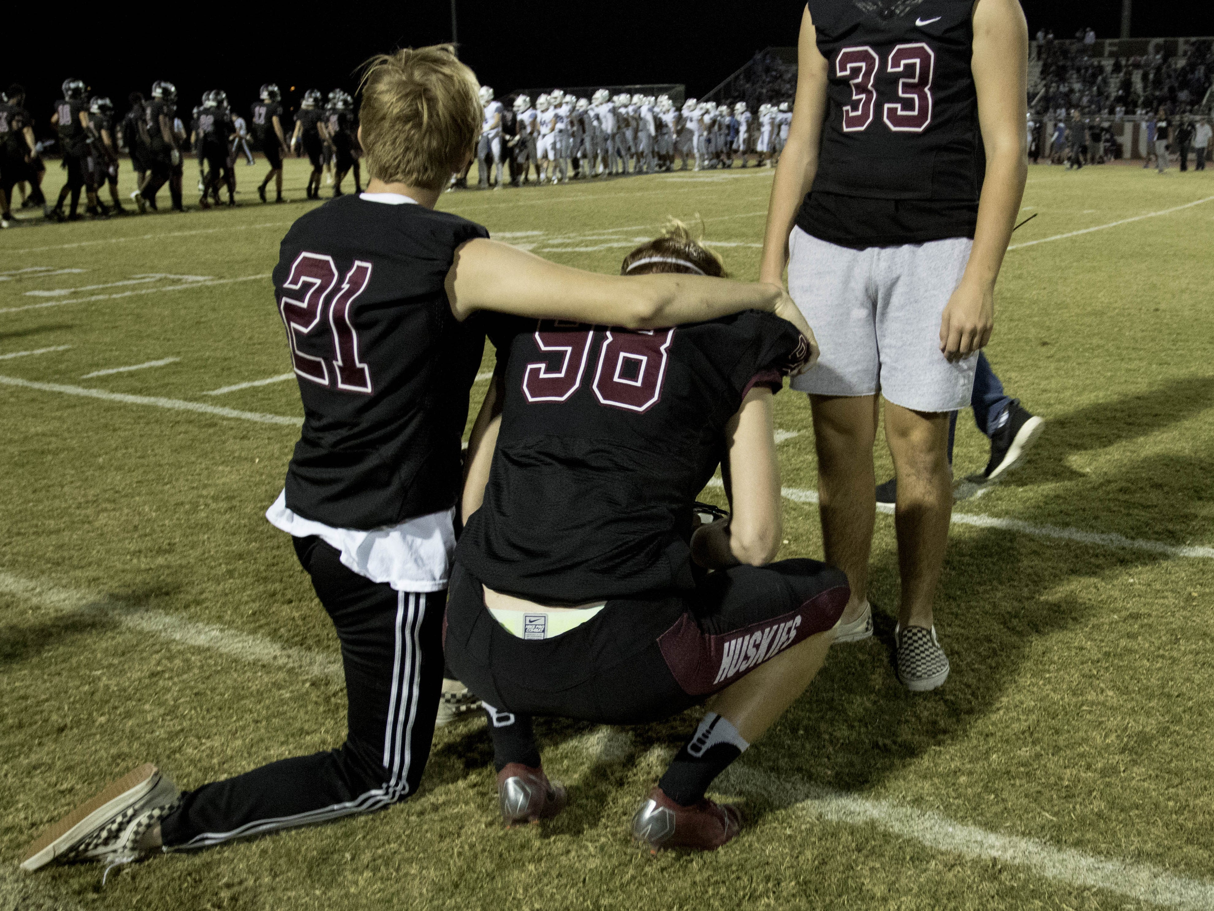 Hamilton senior Daniel Obarski (98) gets consoled by junior teammates Jeremiah Trojan (21) and Jacob Brown (33) after their 49-7 loss over crosstown rival Chandler, Friday, Oct. 26, 2018. #azhsfb