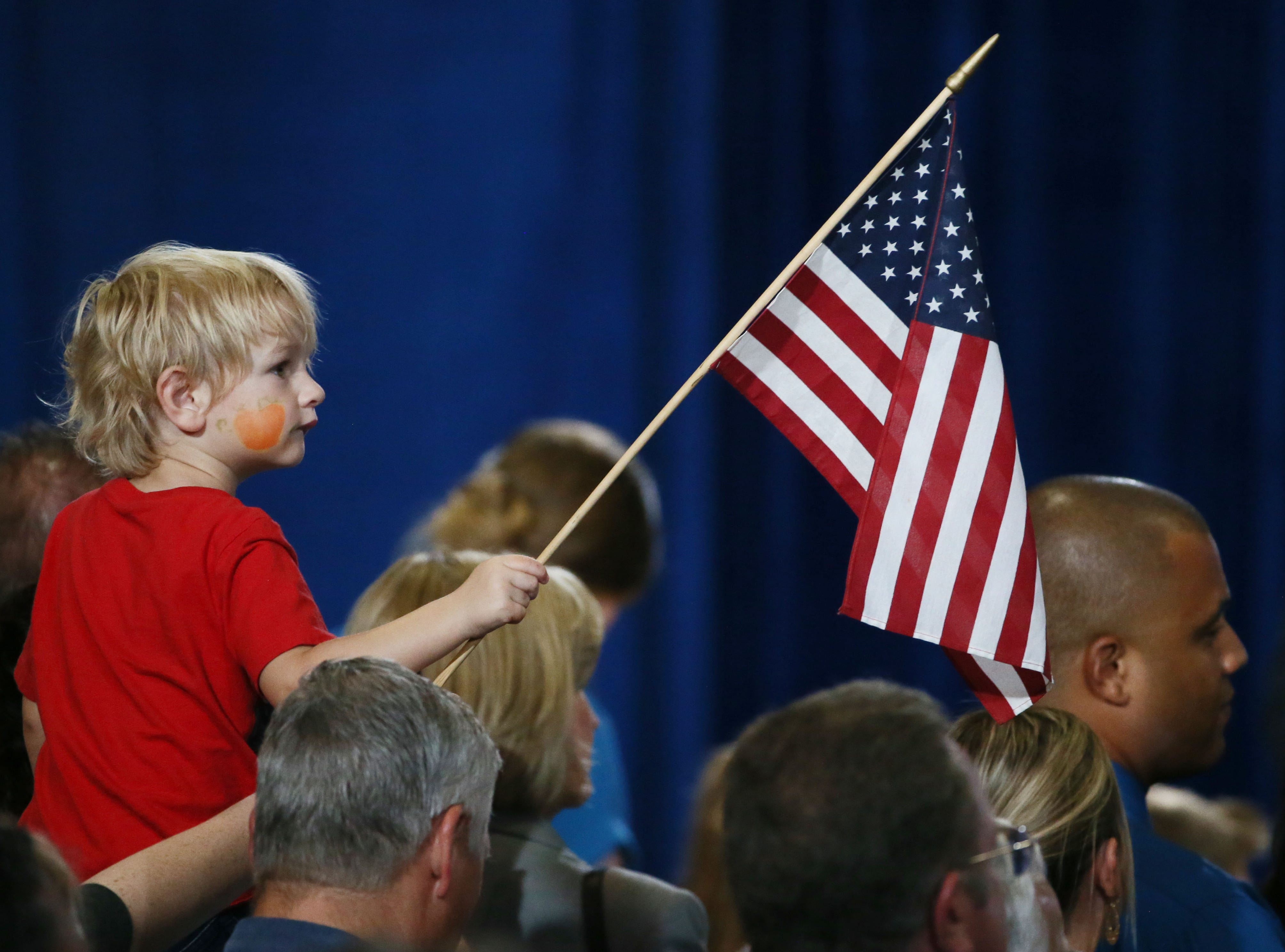 A young boys holds an American flag as Vice President Mike Pence stumps for Republican Senate candidate Martha McSally on Oct. 26, 2018 in Yuma.