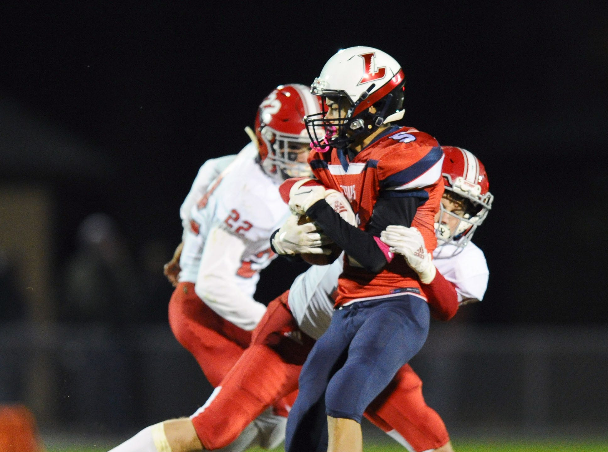 Lebanon's Alexander Rufe (5) runs for a first down as A-C's Daniel Tobias(19) tries to bring him down.
