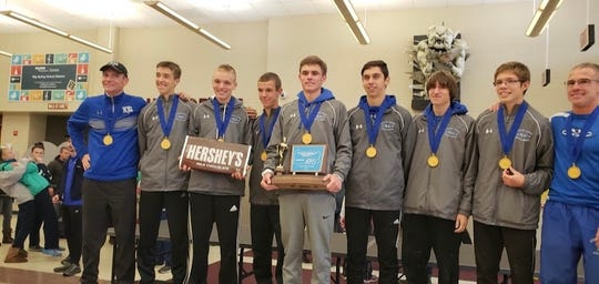 A very happy Cedar Crest boys cross country team shows off the fruits of its labor after capturing the District 3 Class 3A Championship last month.