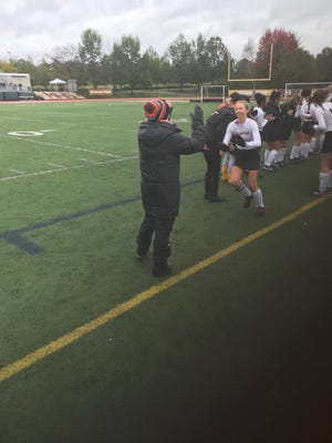 Palmyra's Nicole Shank is greeted by assistant coach Kristi Costello during pregame introductions.