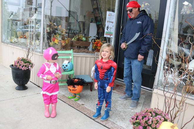 Olivia and Colin Wolan, along with their grandfather Doug Coppeler, pass out candy in front of their family store, Unique, during Port Clinton's annual Downtown Trick-or-Treat on Saturday.