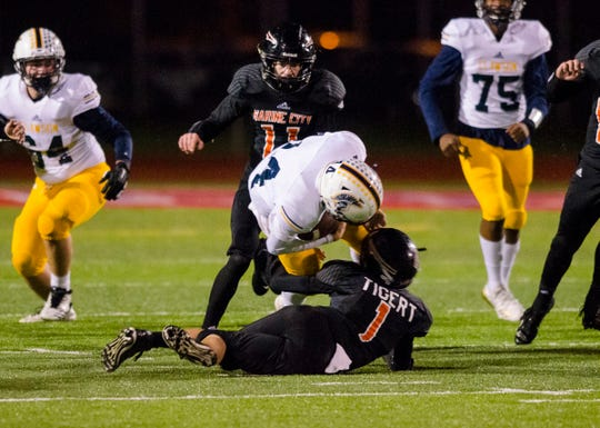 Marine City running back Charles Tigert (1) brings down Clawson's Bryce Blaesing in the first quarter of their D5 pre-district tournament game Saturday, Oct. 27, 2018 at East China Stadium.