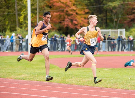Port Huron Northern High School junior Carter Stoner (179) is chased by Avondale High School junior Jibril Syed as he nears the finish line in the division 1 class A regional cross country race Saturday, Oct. 27, 2018, at Algonac High School.