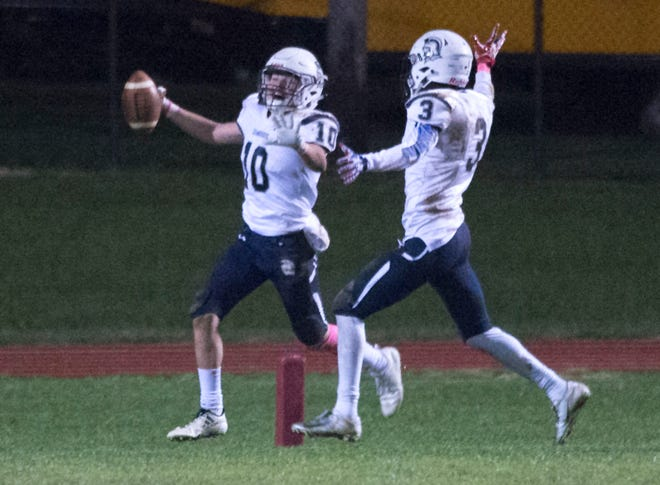 Chambersburg's Brady Hughes (10) celebrates with Tyeshawn Worrell (3) after picking off a pass with seconds remaining in the game to seal the victory during the 26-20 win over Carlisle on Friday, October 26, 2018.