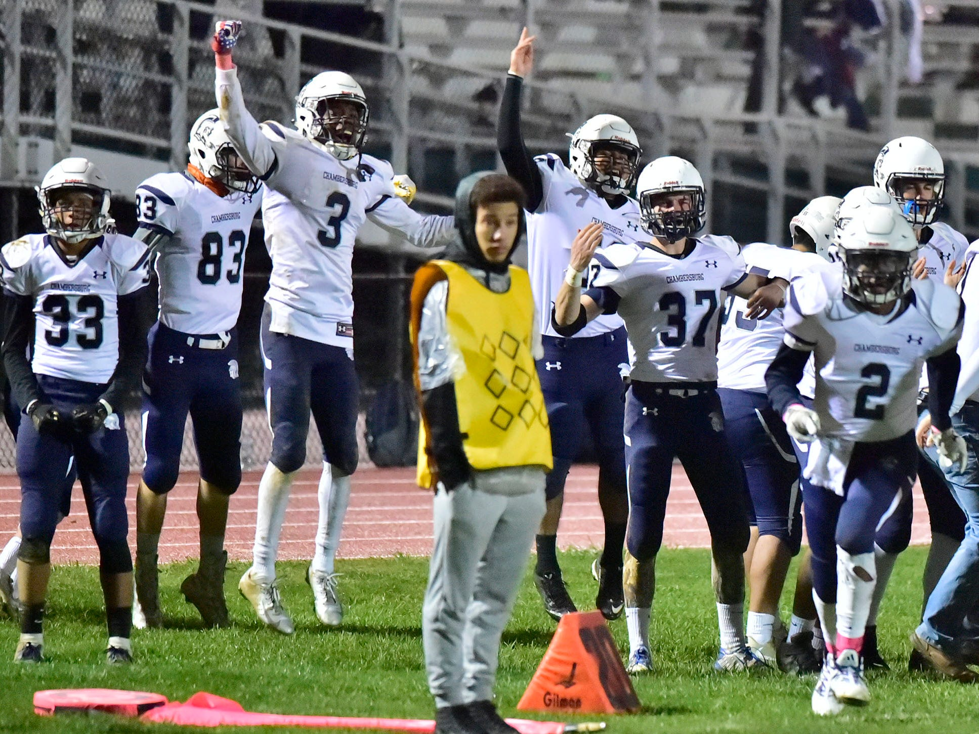 The Chambersburg sideline erupts after a score drive late in the Carlisle game during a 26-20 Trojan victory on Friday, October 26, 2018..
