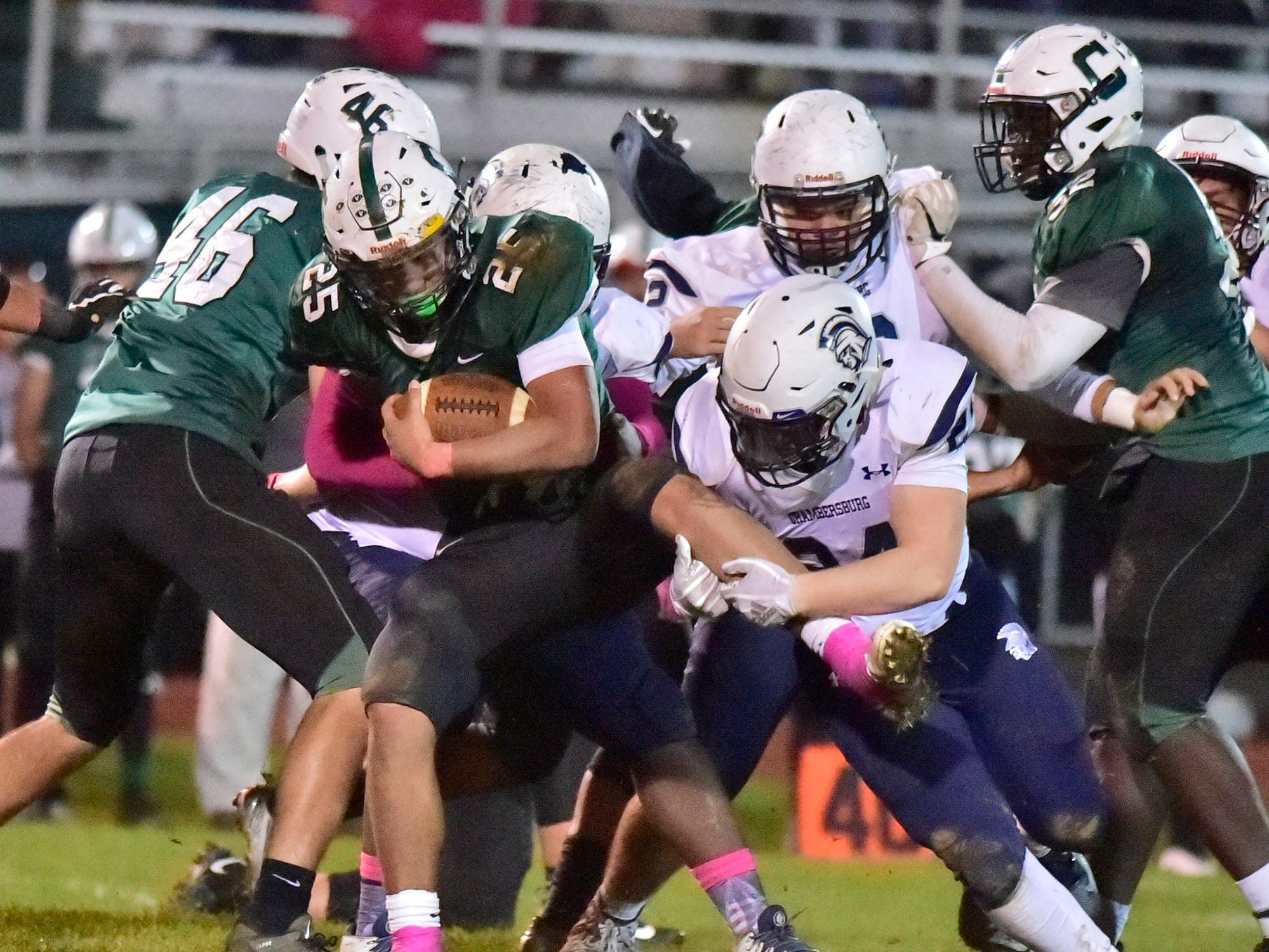 Chambersburg's Andrew Shetter (24) gets a hold of Carlisle's Wyatt Vioral's (25) leg for a tackle during a 26-20 Trojan victory.