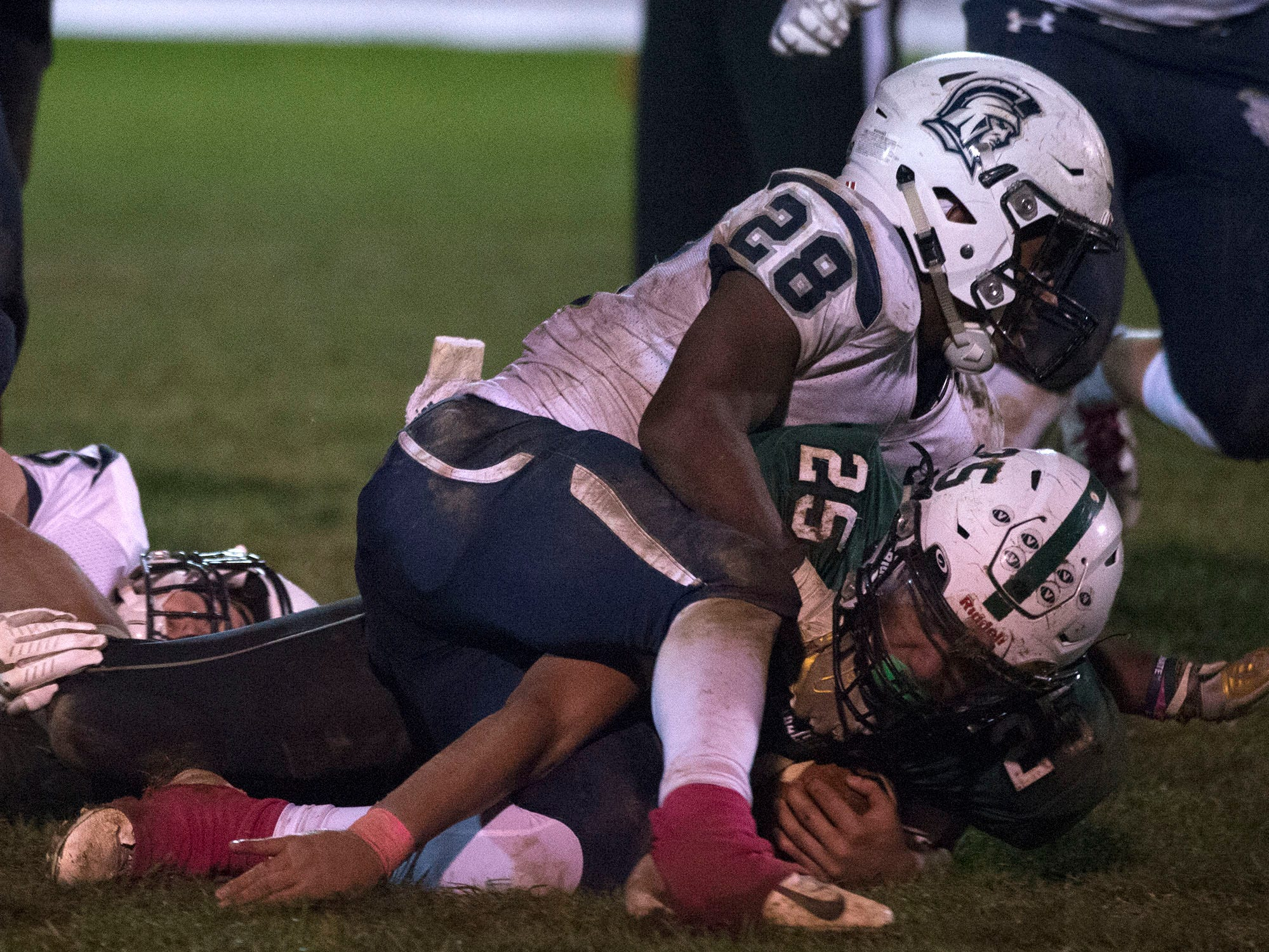 Chambersburg's Keyshawn Jones (28) makes a tackle on Carlisle's Wyatt Vioral (25) during a 26-20 Trojan victory on Friday, October 26, 2018..