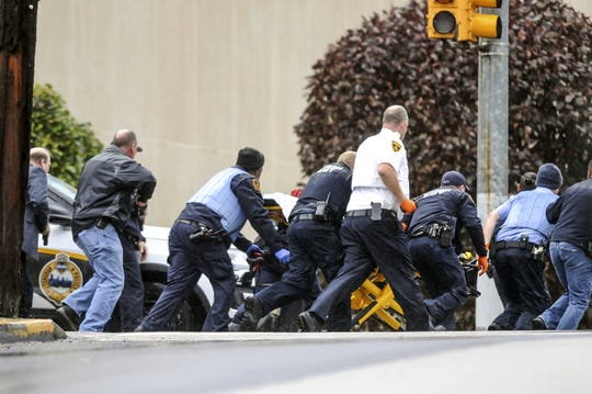 Law enforcement run with a person on a stretcher at the scene where multiple people were shot, Saturday, Oct. 27, 2018, at the Tree of Life Congregation in Pittsburgh's Squirrel Hill neighborhood. (Alexandra Wimley/Pittsburgh Post-Gazette via AP)