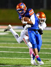 Central York's Jamal Cortez, back, pulls down York High's Tobee Stokes during football action at Small Field in York City, Friday, Oct. 26, 2018. York High would win the game 54-14. Dawn J. Sagert photo