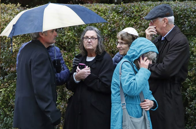 People gather on a corner near the Tree of Life Synagogue in Pittsburgh where a shooter opened fire Saturday, Oct. 27, 2018. (AP Photo/Gene J. Puskar)