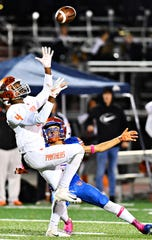 York High's Tino Conquest, back, looks on as Central York's Saa'hir Cornelius receives a pass during football action at Smalls Field in York City, Friday, Oct. 26, 2018. York High would win the game 54-14, sharing the Division 1 title with Red Lion. Dawn J. Sagert photo