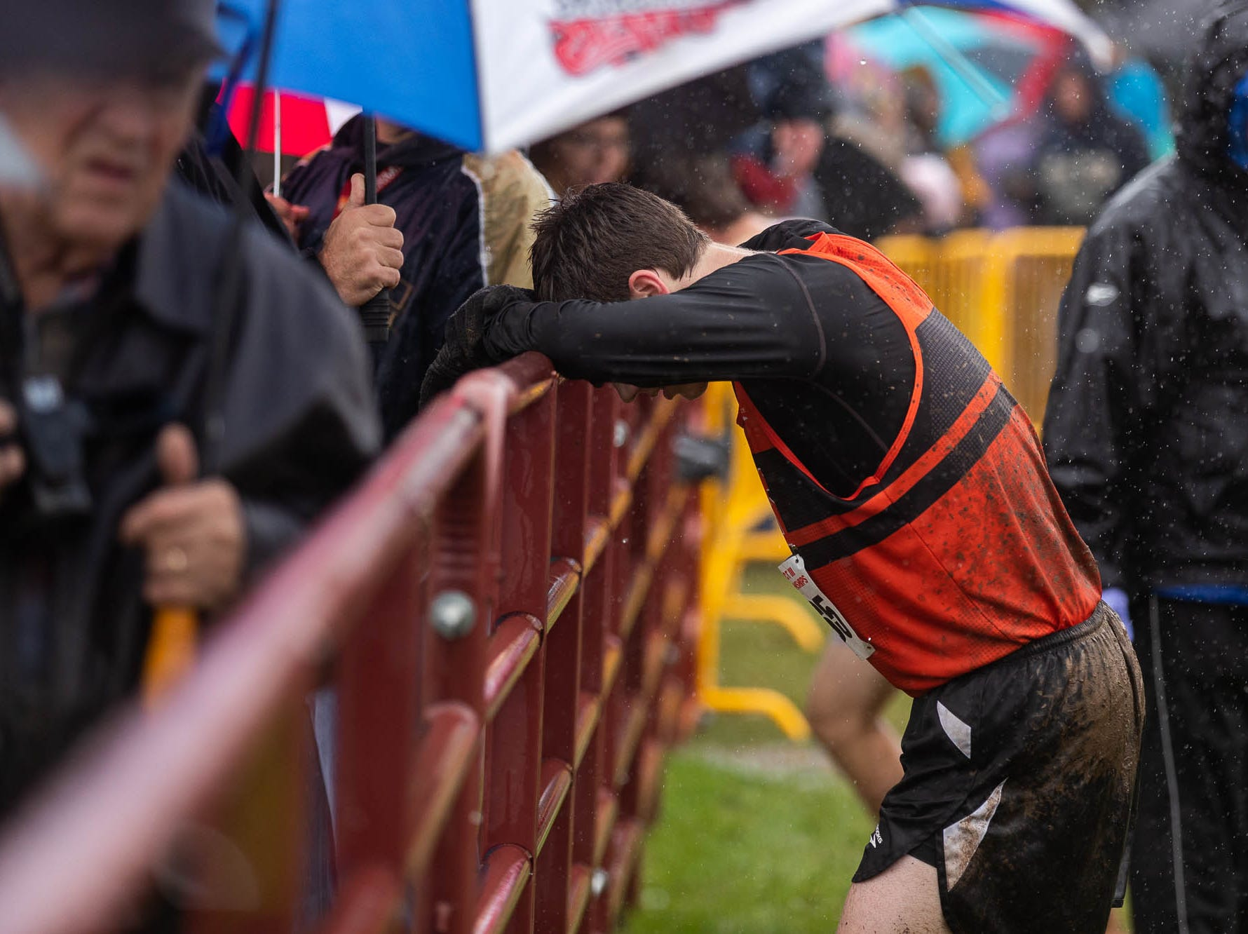 York Suburban's Jordan Ohl (1065) rests on a fence after finishing 26th in the Boys AA race during the PIAA District III Cross Country Championship, Saturday, Oct. 27, 2018, at Big Spring High School in Newville.