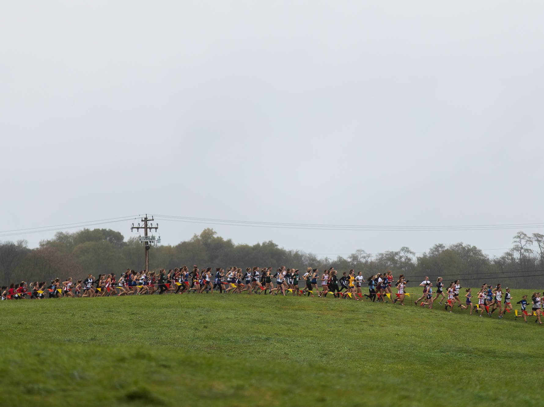 The Girls AAA race rounds the first corner during the PIAA District III Cross Country Championship, Saturday, Oct. 27, 2018, at Big Spring High School in Newville.