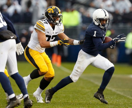 Penn State's KJ Hamler (1) runs out of bounds after a catch as Iowa's Amani Hooker (27) defends during the first half of an NCAA college football game in State College, Pa., Saturday, Oct. 27, 2018. (AP Photo/Chris Knight)
