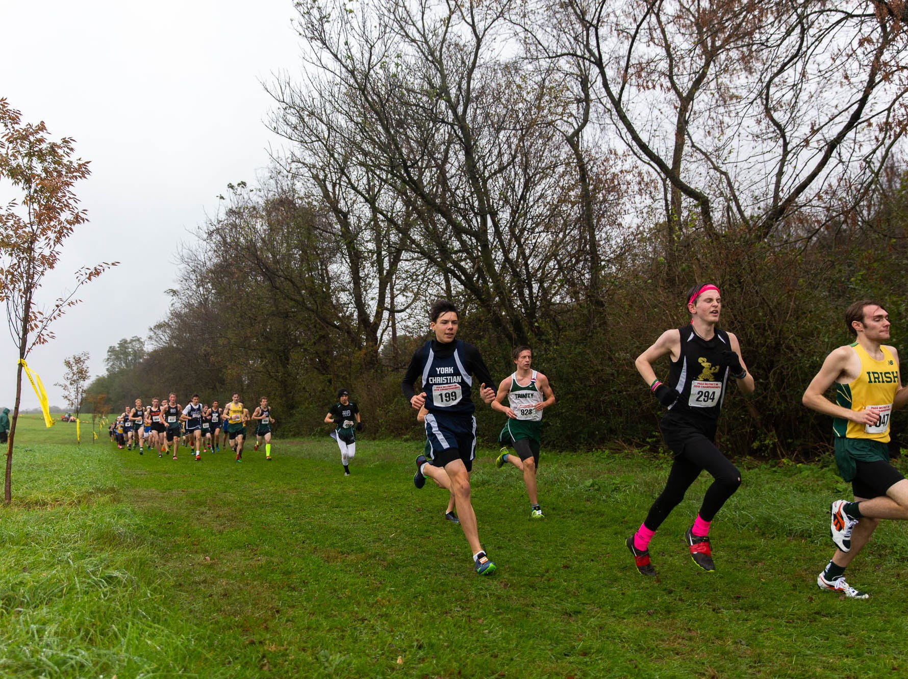 York Christian's Eric Shelton (199), Delone Catholic's Gabe Hall (294), and York Catholic's Christian Gervasi (1047) race in the Boys A during the PIAA District III Cross Country Championship, Saturday, Oct. 27, 2018, at Big Spring High School in Newville.