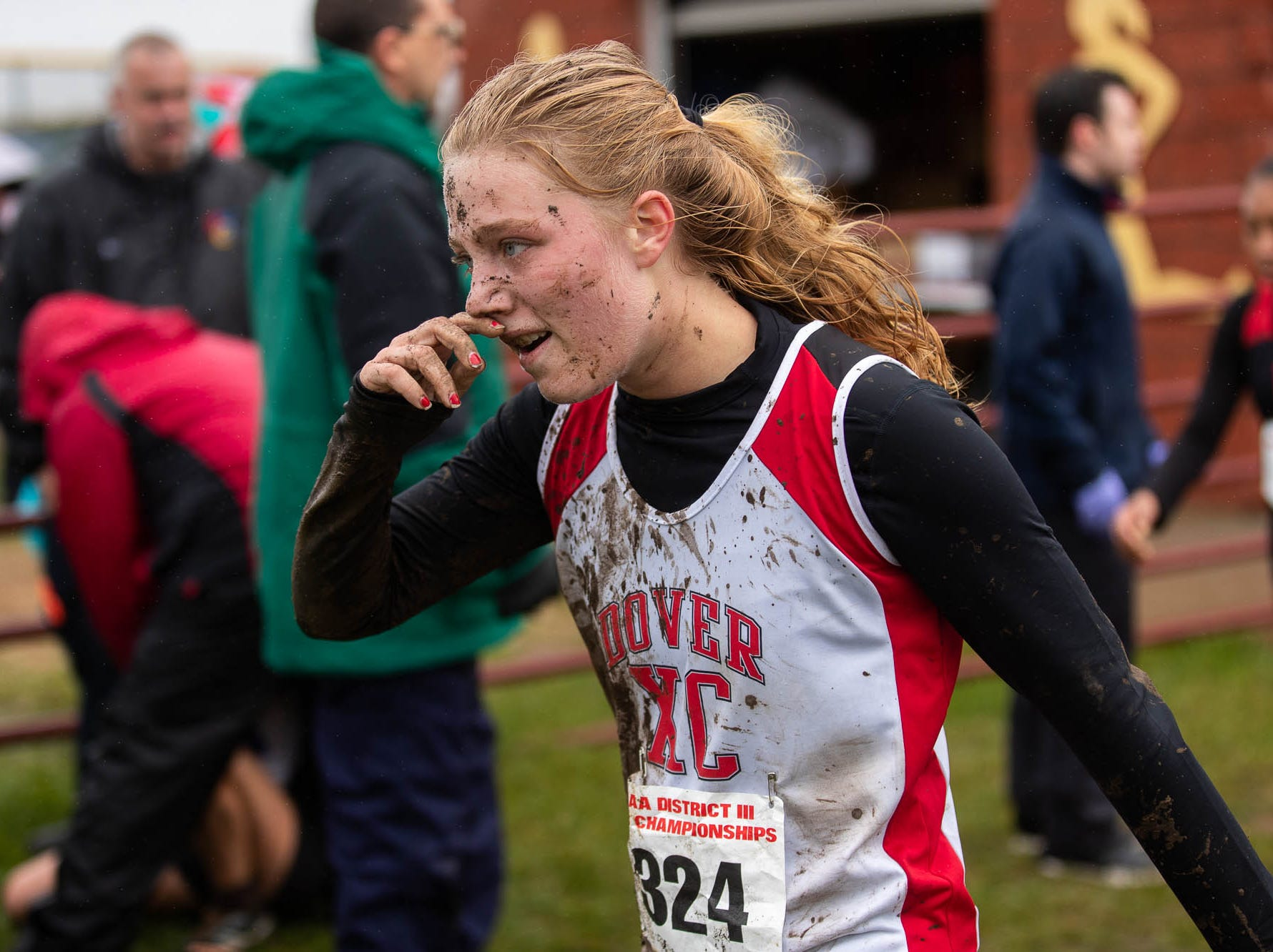 Dover's Emma Burr (324) wipes mud from her face after finishing the Girls AAA race during the PIAA District III Cross Country Championship, Saturday, Oct. 27, 2018, at Big Spring High School in Newville.