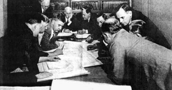 W.S. Shipley, chairman of York Corporation, sits at the head of the table as business leaders study newly received specifications for defense work in World War II. This scene came from a York Corporation newsletter.