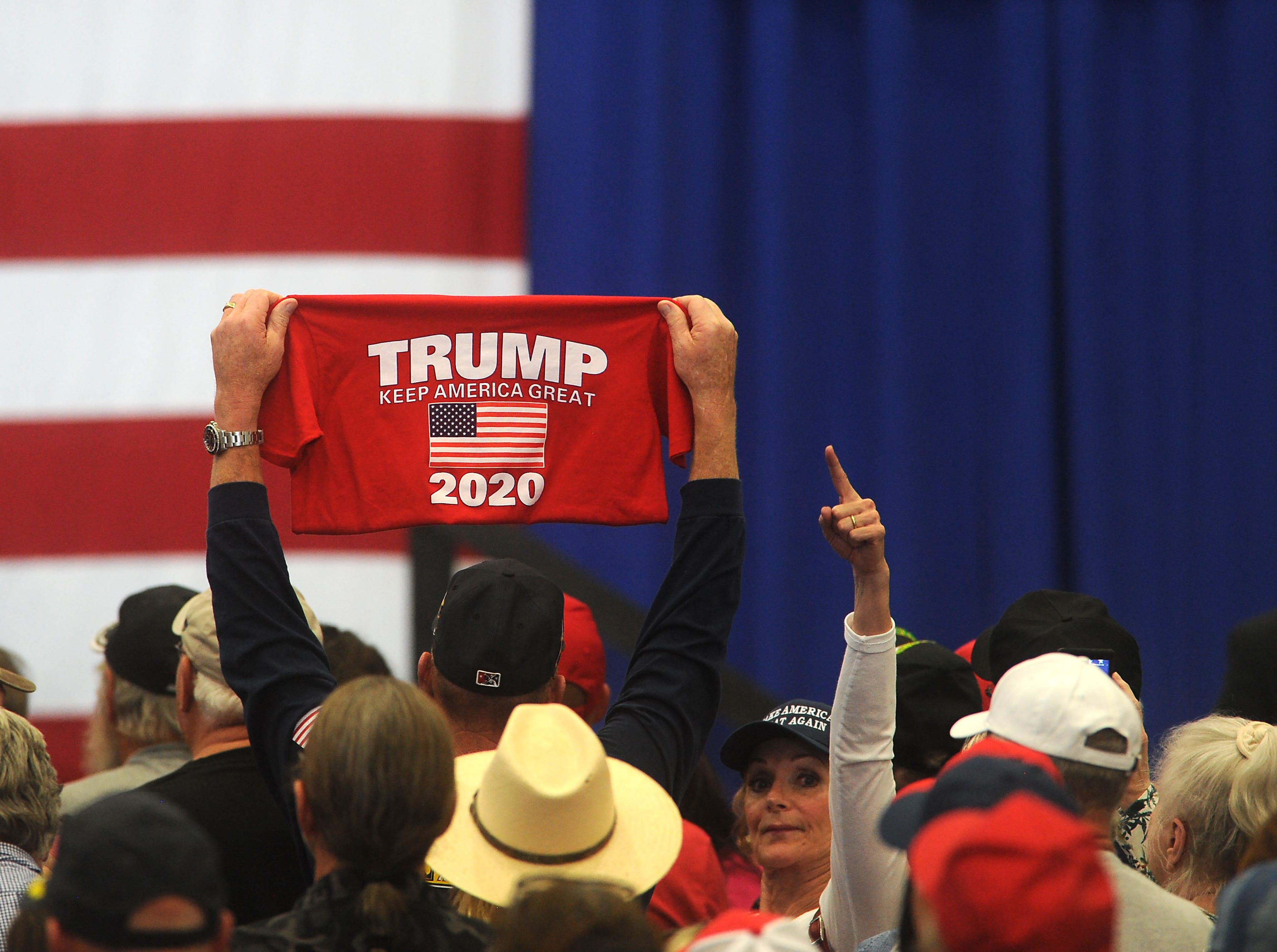 A supporter holds up a Trump shirt as Vice President Mike Pence speaks at the Carson City Airport on Oct. 27, 2018.
