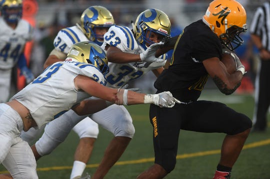 Bishop Manogue's Peyton Dixon (10) runs past the Reed defense for a touchdown during their football game in Reno on Aug. 24, 2018.