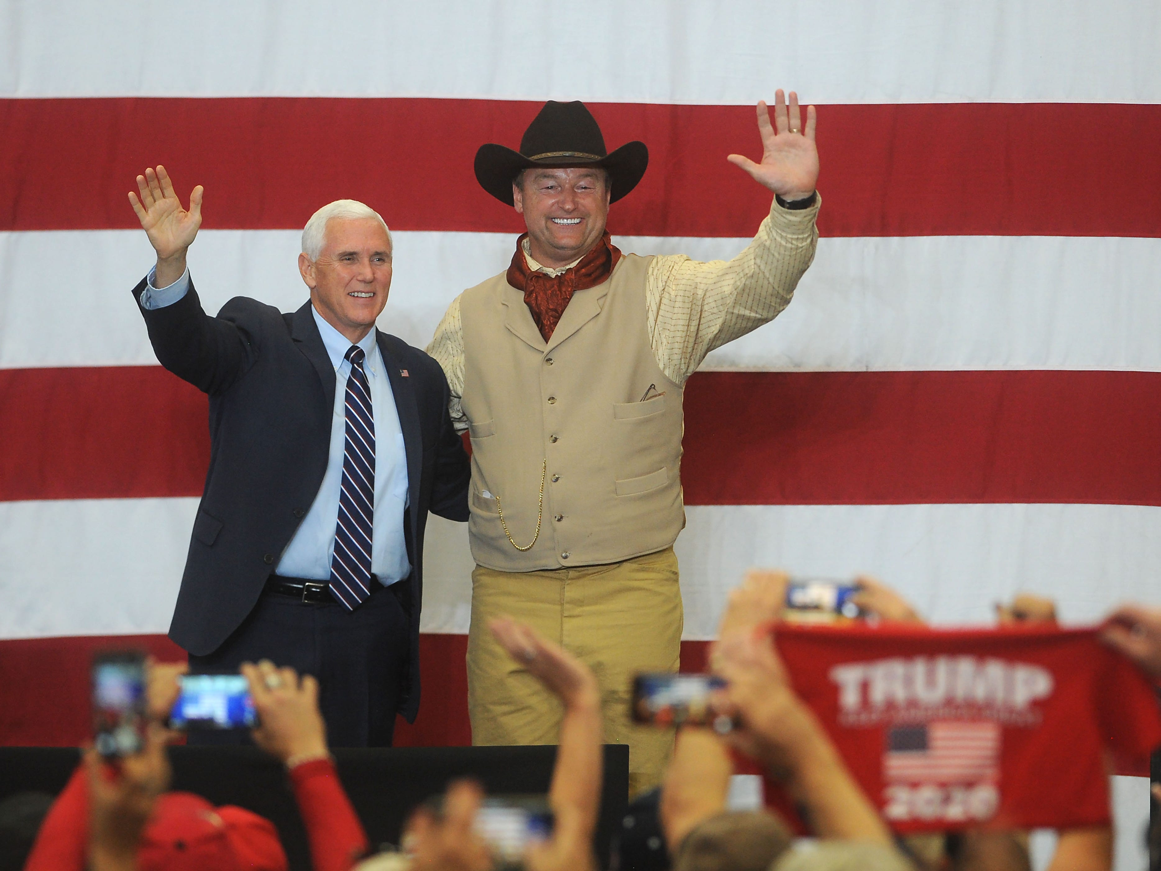 Vice President Mike Pence, left, and U.S. Senator Dean Heller wave to their supporters at the Carson City Airport on Oct. 27, 2018.