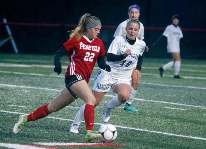 Penfield's Genevieve Foster runs with the ball next to Webster Schroeder's Kara Rieger in the first half at Canandaigua Academy.
