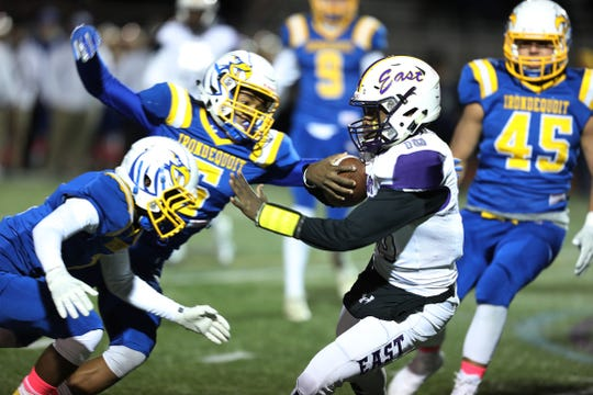 East's quarterback Anthony Gilbert gets stopped by two Irondequoit players.