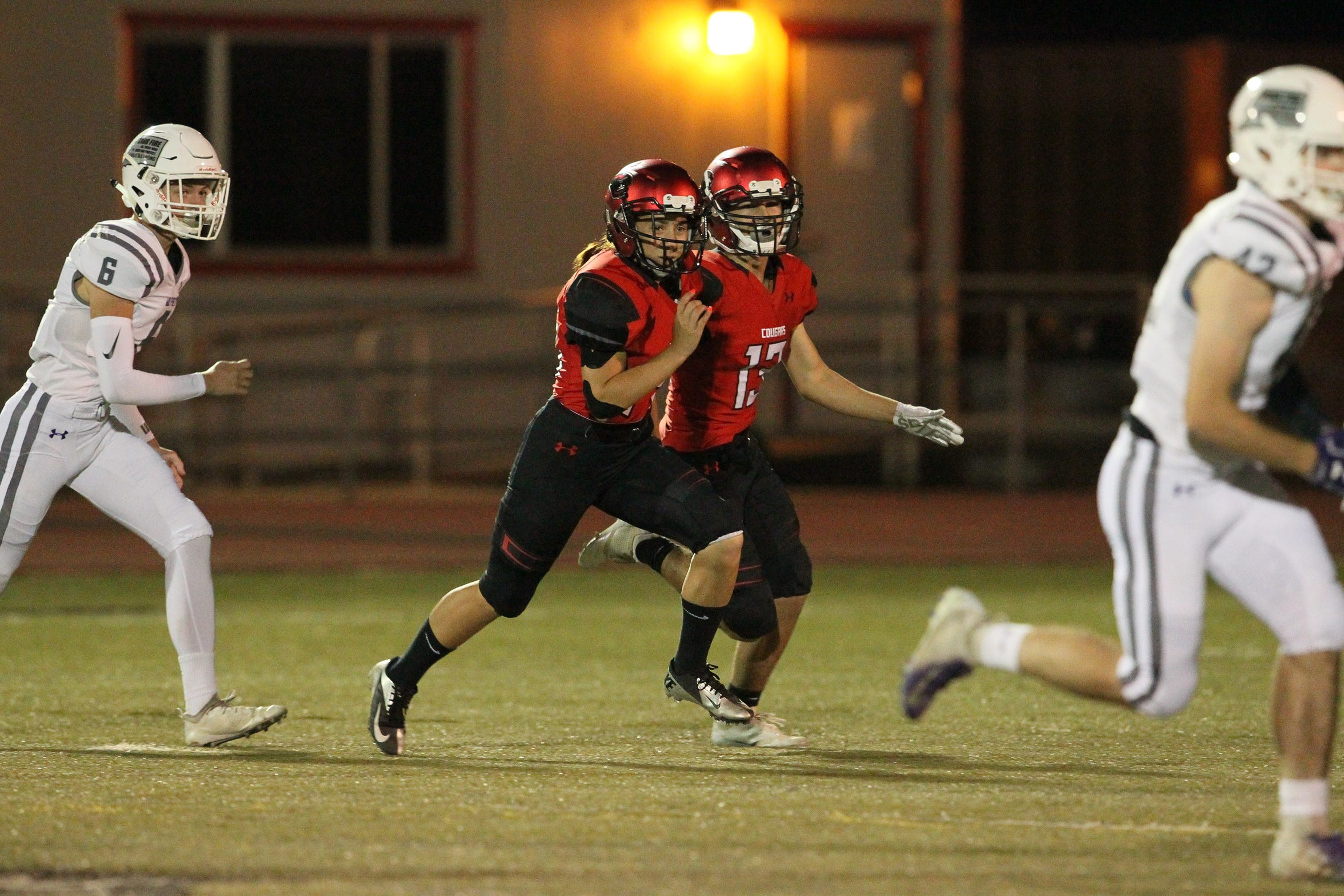 Foothill outside linebacker Lilia Hoheisel (14) and Caleb Wigington (13) move toward the action during their Friday night game against Shasta. Foothill won 49-20.