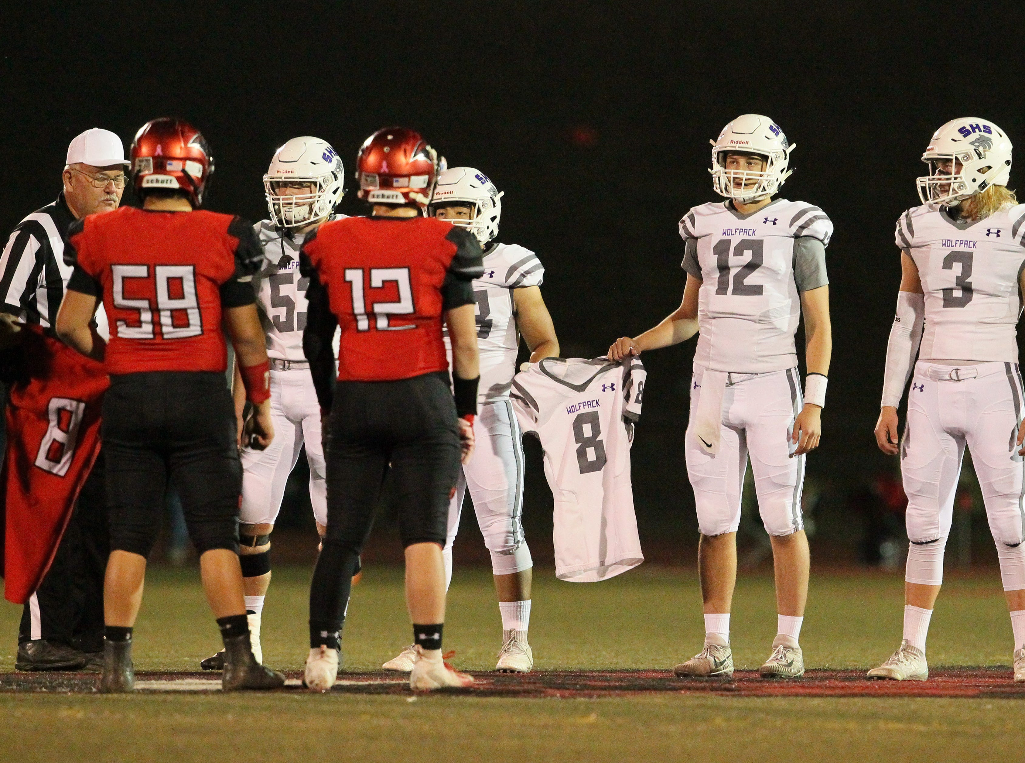Shasta and Foothill carry their No. 8 jerseys to midfield before the game to honor West Valley player Tyson Wacker who died on Monday, Oct. 22 after a crash. Both teams agreed to retire their No. 8 jerseys for the rest of the season.