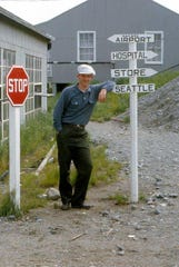 Scott Carter, in his mid-20s, leaning on a signpost in the small town of Naknek, Alaska, at Bristol Bay.