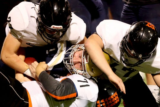 West Albany's Carson Van Dyke (1) is taken down by Silverton's Nathaniel Gubbels (22), Owen Magill (47) and Ayden Russell (71) in the first half of the Silverton vs. West Albany football game at West Albany High School in Albany on Friday, Oct. 26, 2018.