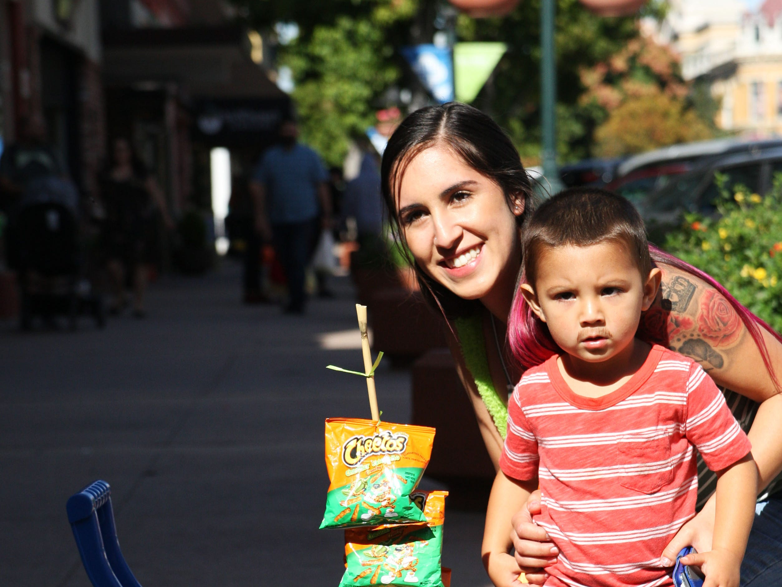 Brenda Samano holds her son, Angelo Raya, posing for a photo beside his paletero cart for trick-or-treating in Oldtown Saturday. Raya shows off his drawn-on mustache.