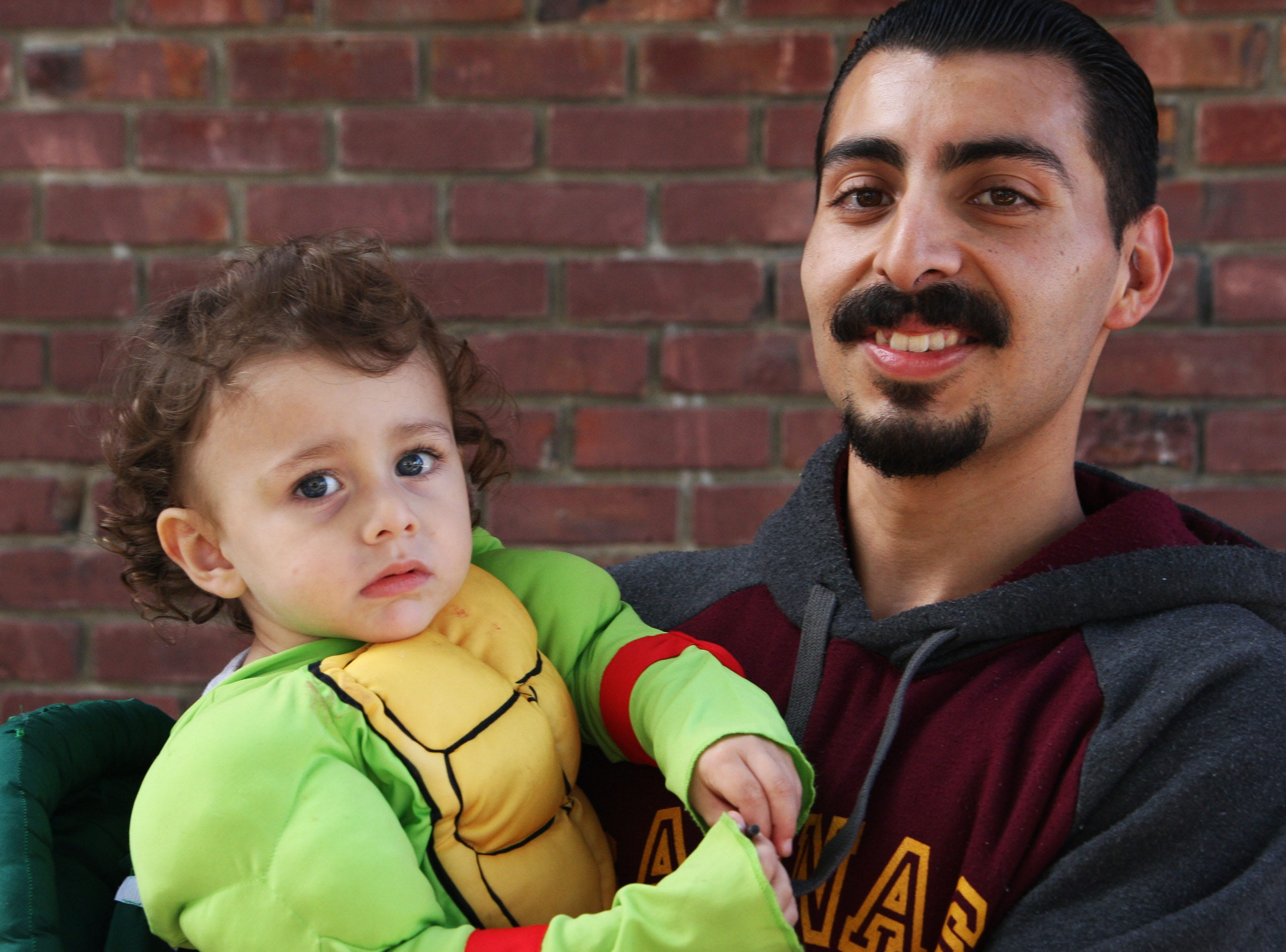 Nehemiah Padilla, 24, holds his son, Nehemiah Saling, 2, as they prepare to go trick-or-treating in Oldtown Saturday. Saling, Nehemiah's mother Britani Saling says, just learned what a pumpkin is.