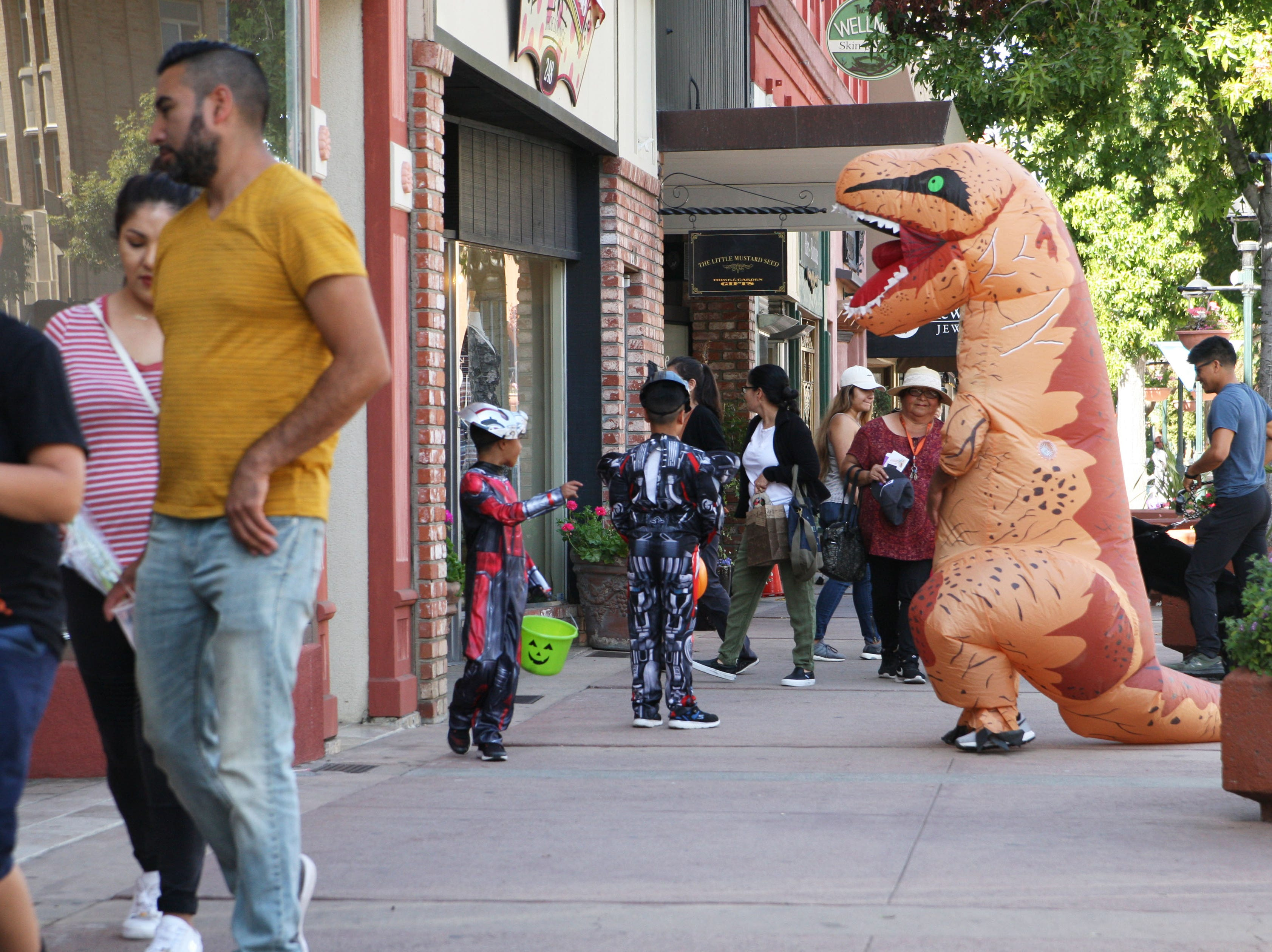 A Tyrannosaurus Rex menaces the Leon family in Oldtown during trick-or-treating.