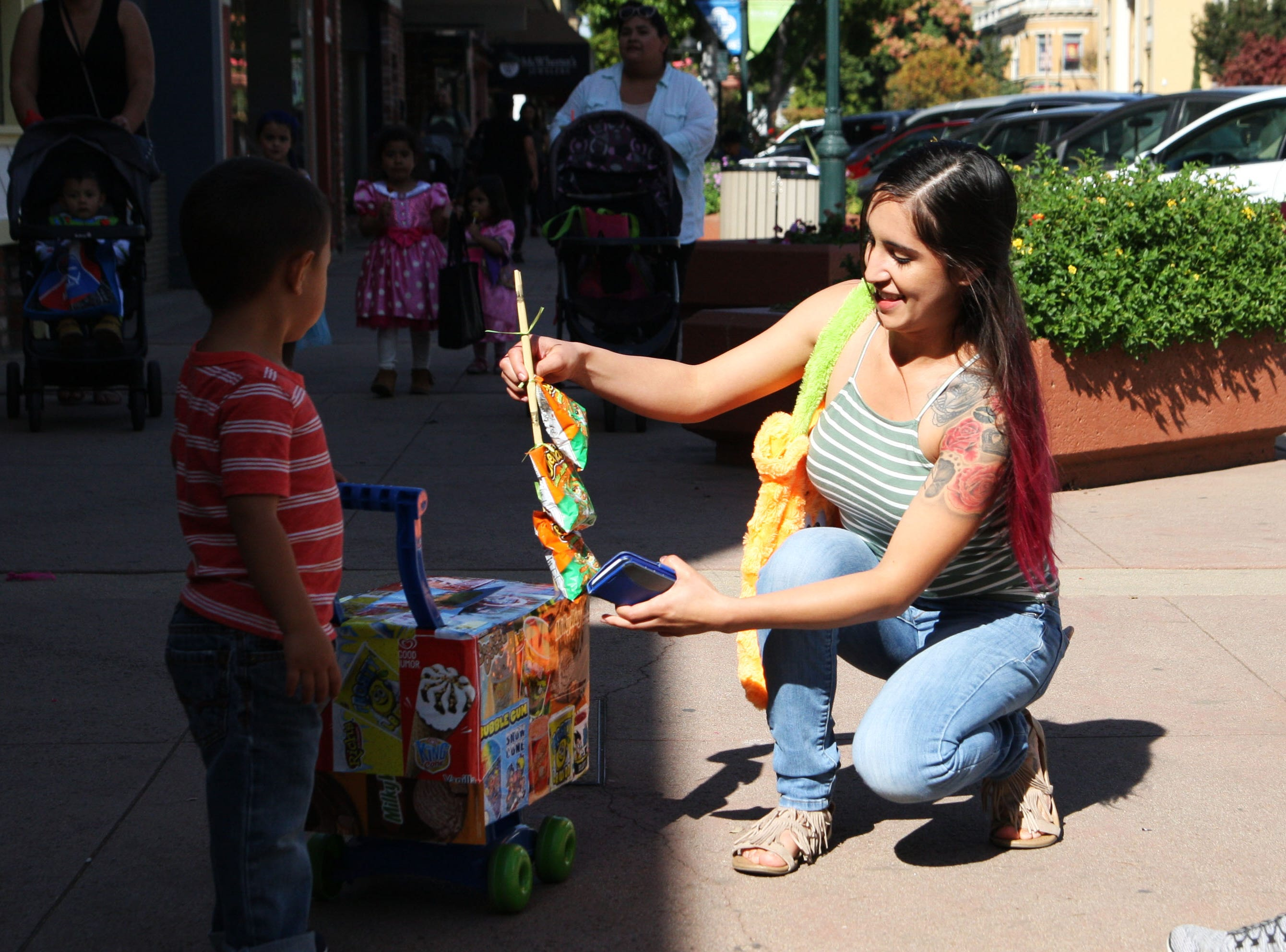 """Brenda Samano helps her son, Angelo Raya, 2, with his paletero costume in Oldtown Saturday. """"He loves ice cream and he always chases after (the paletero), so I made this costume,"""" said Samano. """"He loves it, he wouldn't let it go."""""""
