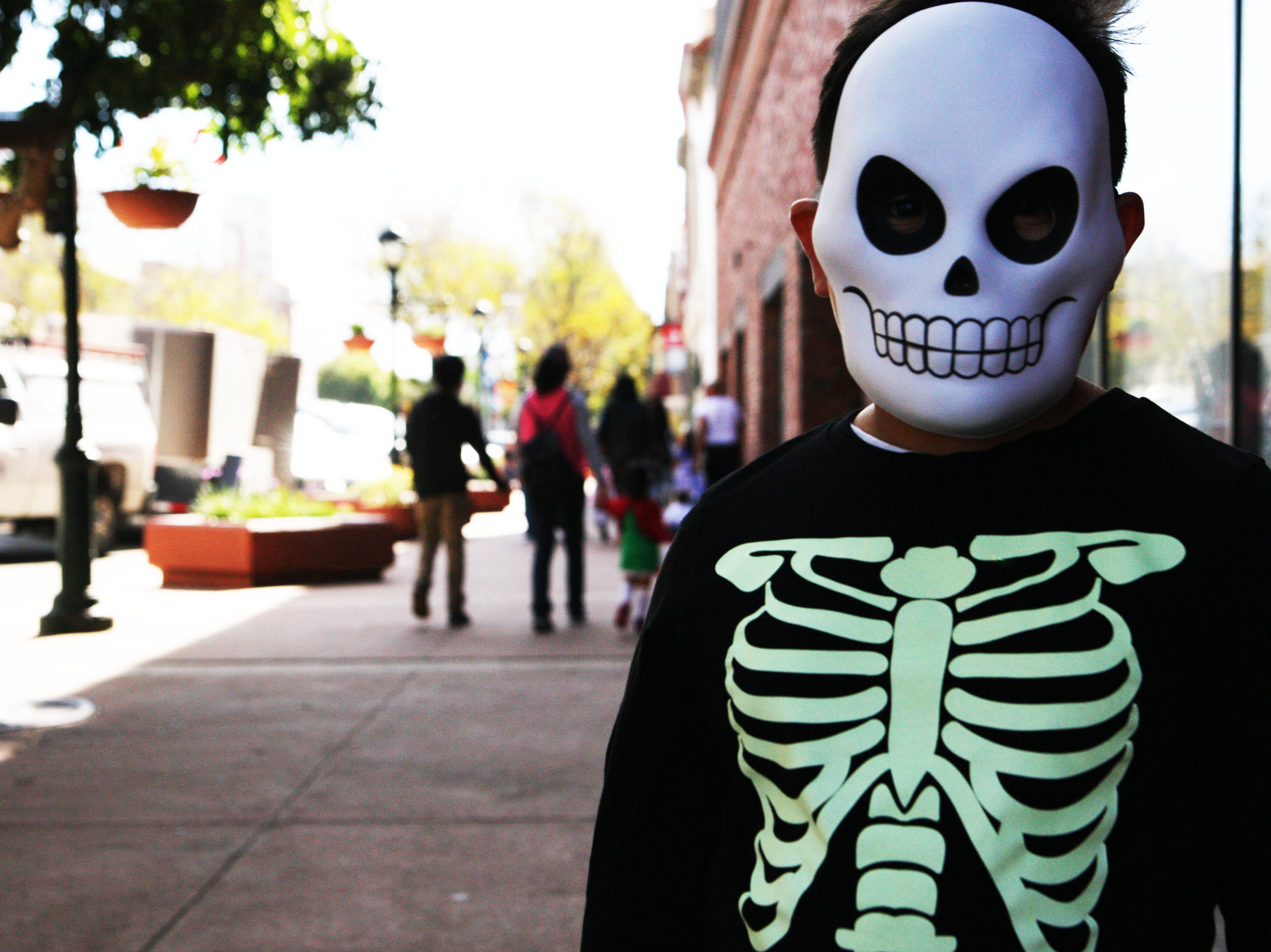 Jacob Torres, 8, poses for a photo after going trick-or-treating through Oldtown Saturday with his family, Emma Garcia, and Raymond Garcia. His favorite candy is a Twix bar, he says.