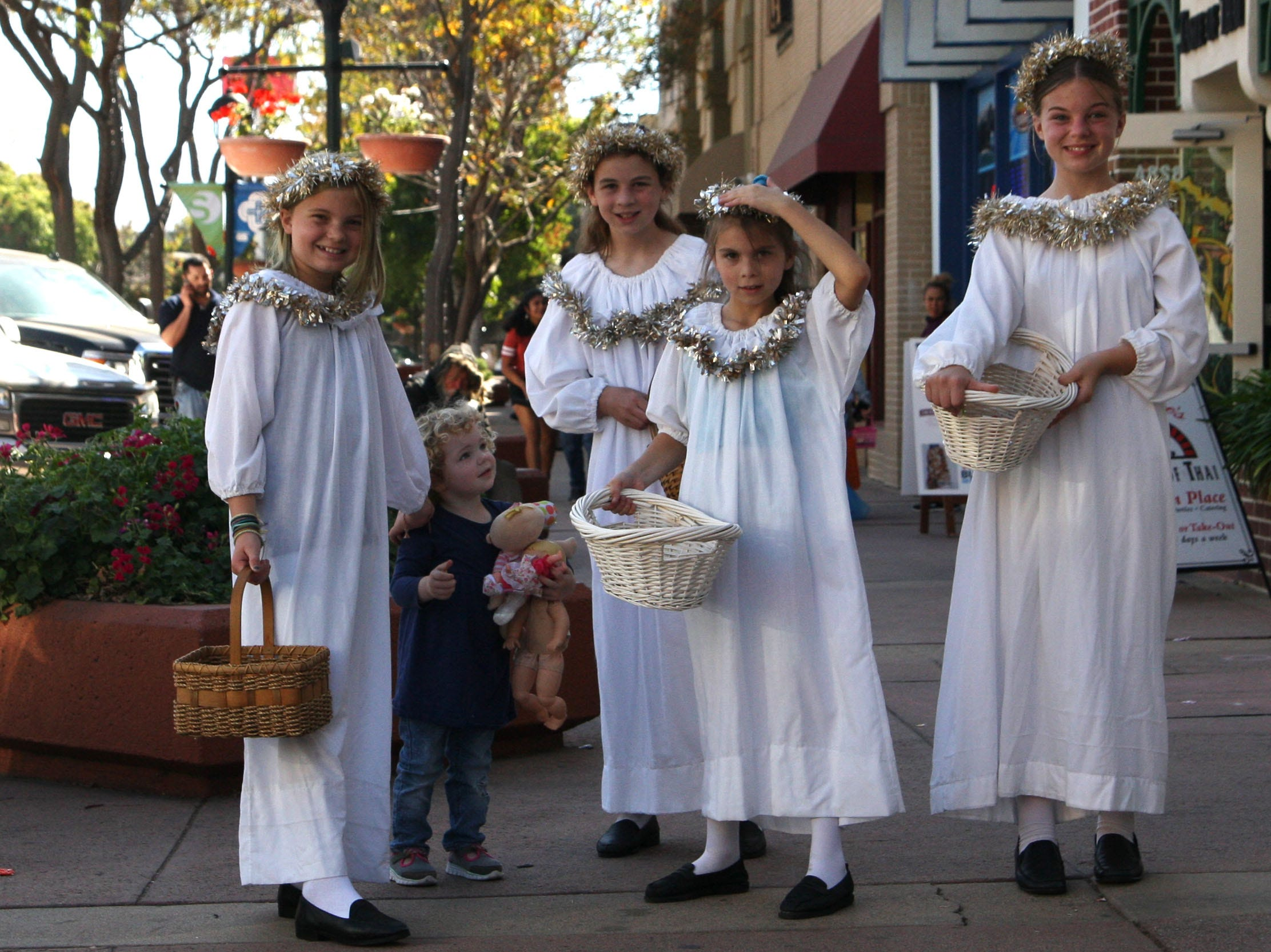 Sophie Staker, Scarlett Staker, Kaelyn Hayward and Tristyn Hayward dress up as angels Saturday in Oldtown to promote their play while trick-or-treating was taking place.