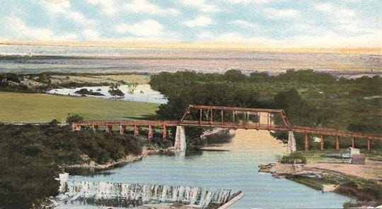 This colorized postcard shows Lone Wolf Bridge in San Angelo as it appeared in 1905, and was taken from a photograph captured by M.C. Ragsdale. The city's water treatment plant is just below the dam seen here.