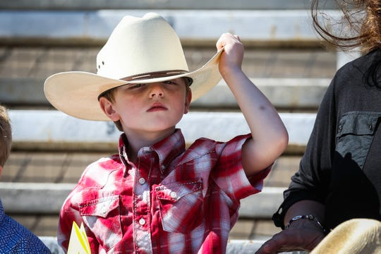A young spectator adjusts his hat during Cinch Roping Fiesta Saturday, Oct. 27, 2018, at the Outdoor Roping Arena.