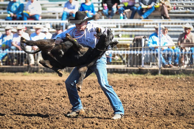 Tuf Cooper ties down a calf during Cinch Roping Fiesta Saturday, Oct. 27, 2018, at the Outdoor Roping Arena.