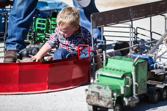 JR Hankins, 1, plays with farm model toys Saturday, Oct. 27, 2018, during Cinch Roping Fiesta.