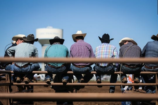 Cowboys sit on the railing to watch the calf roping during the 2018 Cinch Roping Fiesta.