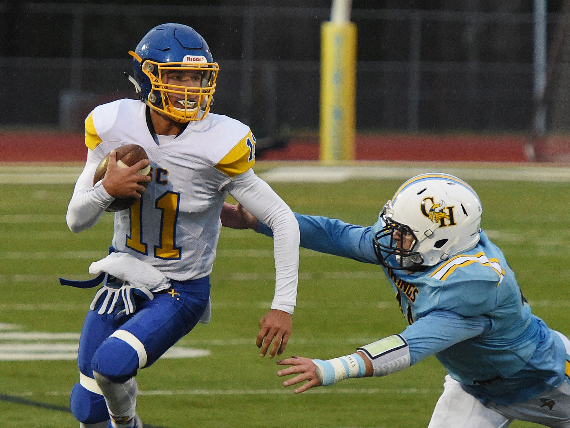 Sussex Central's QB  Isaac Barnes runs for some yardage from Cape's  William Ott during their game Oct. 26, 2018 in Lewes.