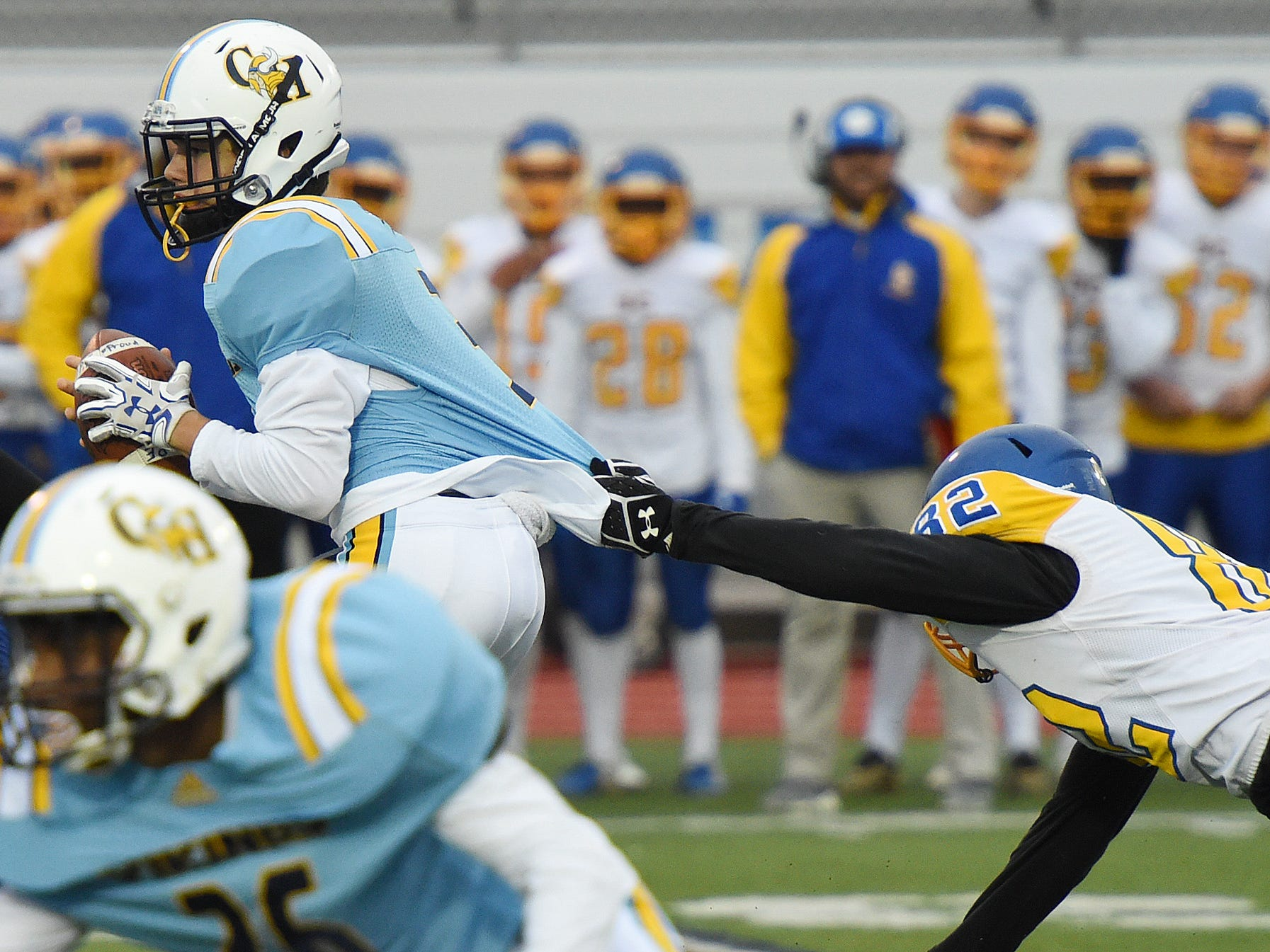 Cape's quarterback Samuel Jones gets pulled down by Sussex Central's  Corgan McGlothan during the game in Lewes on Oct. 26, 2018.