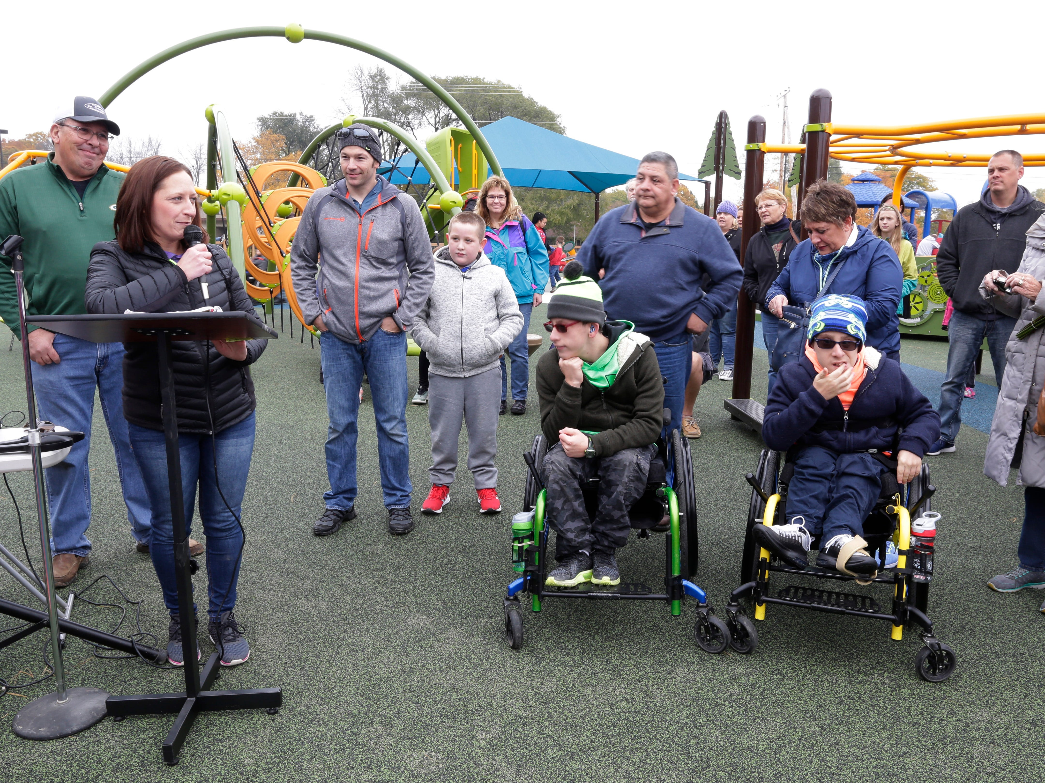 Angie Shaw, left, at podium, spoke of her appreciation for Sheboygan in making her dream of the Shaw Family Playground become reality, Saturday, September 27, 2018, in Sheboygan, Wis. The playground is accessible for children of all physical abilities.